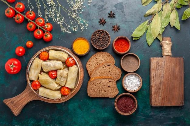 Vista dall'alto gustosa farina di carne arrotolata all'interno di cavolo con pane e pomodori freschi sulla scrivania blu scuro