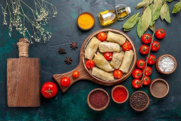 紺色の机の上に調味料オイルとフレッシュトマトを添えてキャベツに巻いたトップビューのおいしい肉骨粉