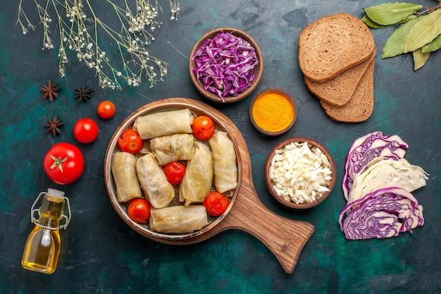 ダークブルーの机の上にパンとオリーブオイルを添えたドルマと呼ばれるキャベツとトマトを巻いたトップビューのおいしい肉骨粉