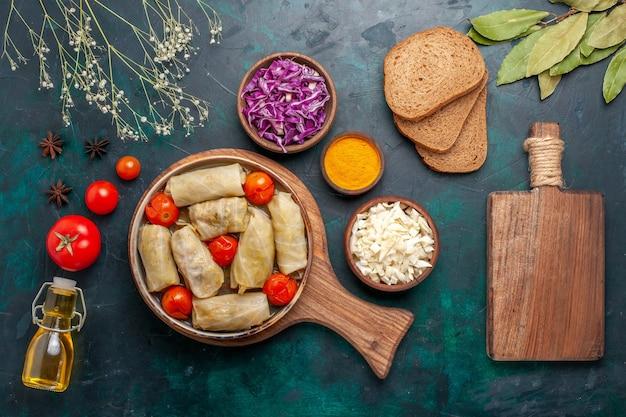 Вид сверху вкусной мясной муки с капустой и помидорами, называемой долма с оливковым маслом и хлебом на темно-синем столе