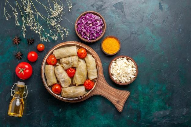 濃紺の机の上にオリーブオイルとドルマと呼ばれるキャベツとトマトを巻いた上面図おいしい肉骨粉