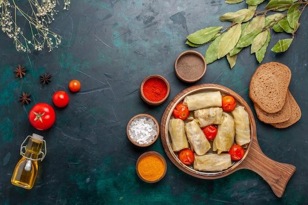 Вид сверху вкусной мясной еды с капустой и помидорами под названием долма с приправами на темно-синем столе