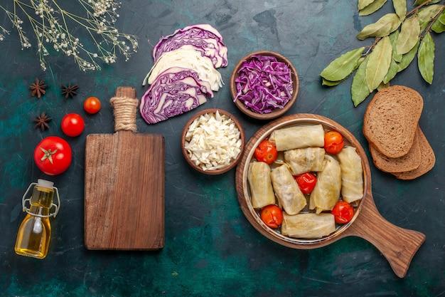 Vista dall'alto gustosa farina di carne arrotolata con cavolo e pomodori chiamati dolma con olio sulla scrivania blu scuro