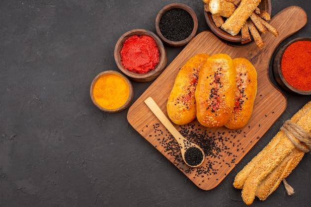 회색 배경 패티 반죽 과자 빵 식사에 조미료와 상위 뷰 맛있는 고기 버거 구운 파이