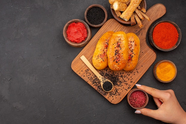 トップビューおいしい肉のパテは灰色の背景に調味料でペストリーを焼いたパティ生地のペストリーの食事