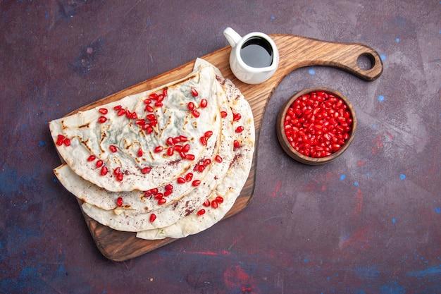 Vista dall'alto qutab di carne saporita pitas con melograni rossi freschi su pita di pasta di carne di cibo superficie viola scuro