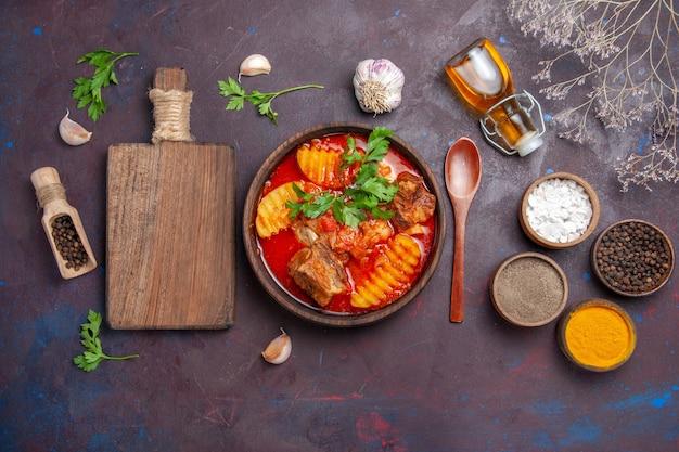 Vista dall'alto gustosa zuppa di ragù di carne con diversi condimenti sul nero