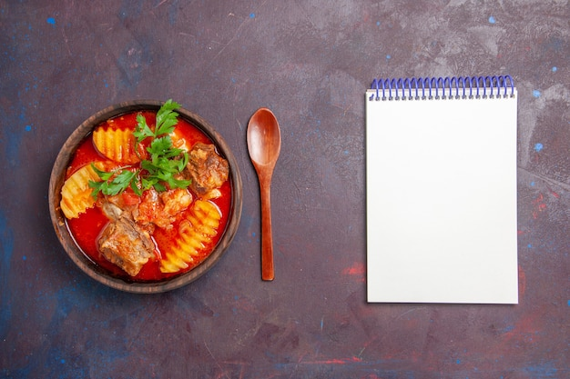Vista dall'alto gustosa zuppa di ragù di carne con verdure e patate a fette sul nero