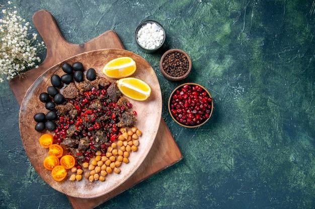 Вид сверху вкусные кусочки мяса жареная еда с виноградом и фасолью внутри тарелки, блюдо
