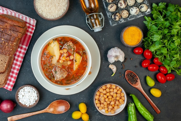 Top view tasty meat soup consists of potatoes meat and beans on a dark background