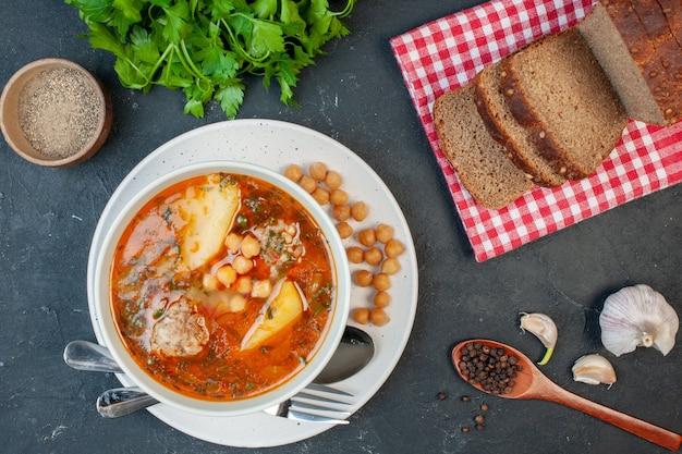 Vista dall'alto gustosa zuppa di carne con pagnotte di pane scuro su sfondo scuro
