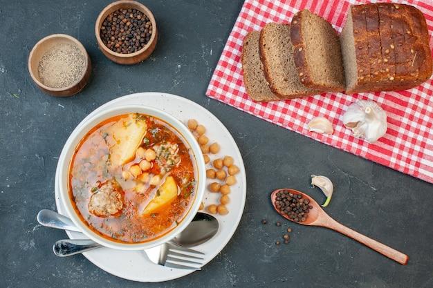 어두운 배경에 어두운 빵 덩어리가 있는 맛있는 고기 수프