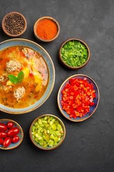 暗いテーブルの上の新鮮な野菜とおいしい肉のスープを上から見た料理料理の写真の食事