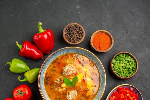 暗いテーブルの食べ物の写真の色の皿に新鮮な野菜とトップビューのおいしい肉のスープ