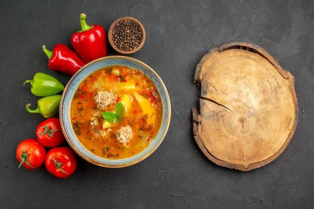 暗いテーブルの上の新鮮な野菜とおいしい肉のスープの上面図写真料理食用色素