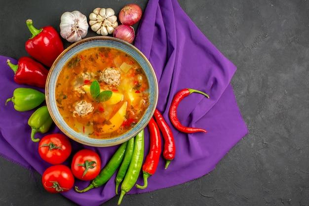 Вид сверху вкусный мясной суп со свежими овощами на темном столе фото пищевой краситель