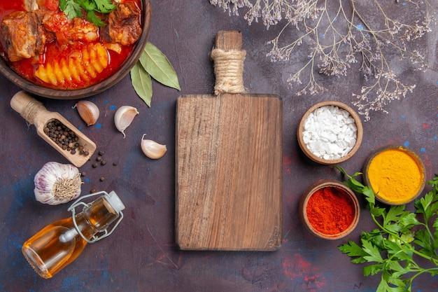 Vista dall'alto gustosa zuppa di carne con aglio e condimenti sul nero