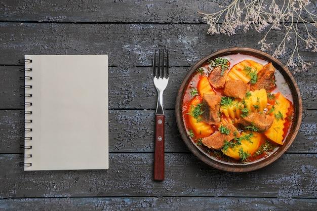 Vista dall'alto gustosa zuppa di carne con verdure e patate sulla scrivania scura