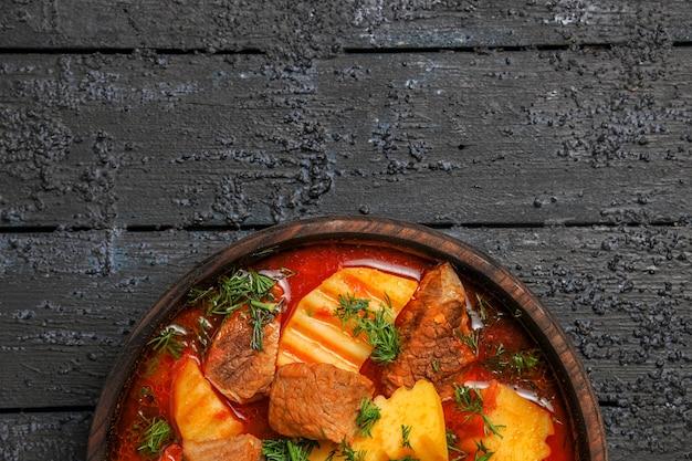 어두운 책상에 감자와 채소가 들어간 맛있는 고기 수프