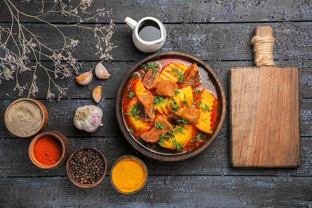 Вид сверху вкусный мясной суп с картофелем и приправами на темном столе