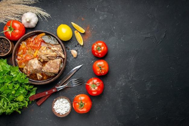 トップビューダークソースミールディッシュにトマトとグリーンを添えたおいしいミートスープホットフードミートポテトカラー写真ディナー料理