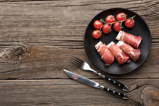 Вид сверху вкусного мяса с помидорами на тарелке