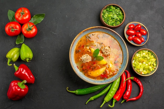 Top view tasty meatballs soup with greens and pepper on dark floor sauce dish color