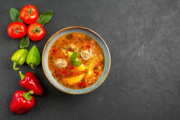 ダークテーブルソース皿の色に野菜とおいしいミートボールスープの上面図