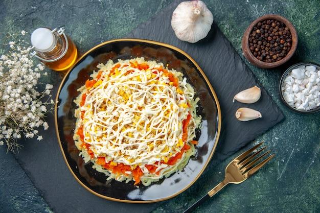 Vista dall'alto della gustosa insalata di mimosa all'interno del piatto sulla superficie blu scuro