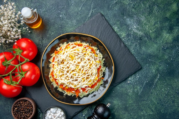 Vista dall'alto della gustosa insalata di mimosa all'interno del piatto con pomodori rossi su superficie blu scuro