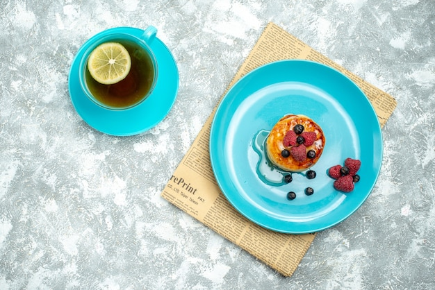 Top view of tasty muffins with berries and cup of tea on light surface
