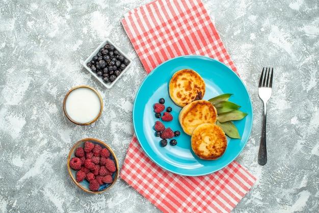 Vista dall'alto di gustosi muffin con frutti di bosco sulla superficie chiara