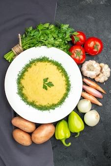Vista dall'alto di gustose purè di patate con verdure e verdure fresche sul tavolo nero