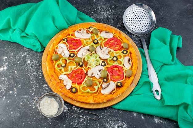 Vista dall'alto gustosa pizza ai funghi con pomodori rossi olive funghi tutti affettati all'interno con olio su sfondo grigio tessuto verde pasta per pizza italiana