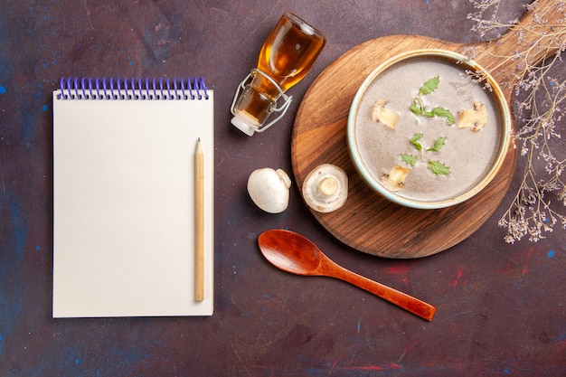 Vista dall'alto gustosa zuppa di funghi all'interno della piastra su sfondo scuro minestra di verdure pasto cena cibo