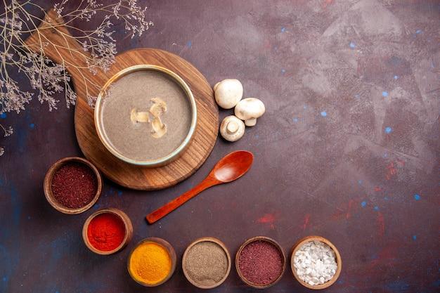 Top view tasty mushroom soup with different seasonings on a dark background soup meal mushroom seasonings food