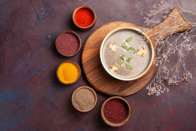 Top view tasty mushroom soup with different seasonings on dark background soup vegetables meal dinner food