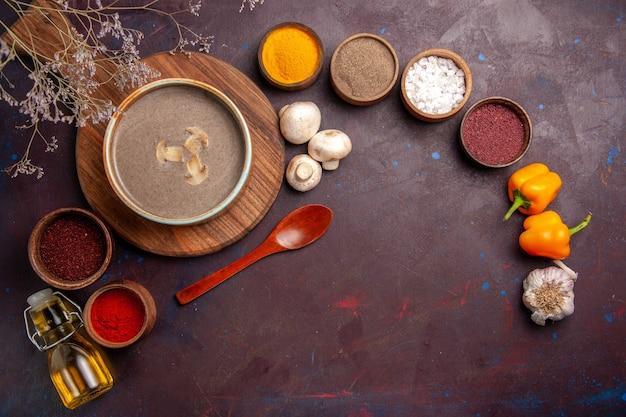 Vista dall'alto gustosa zuppa di funghi con diversi condimenti sul pasto di cibo di condimento a base di zuppa di funghi scura