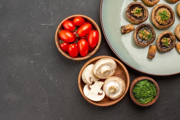 上面図暗い表面の皿に新鮮なトマトと緑のおいしいキノコの食事夕食の食事調理キノコ