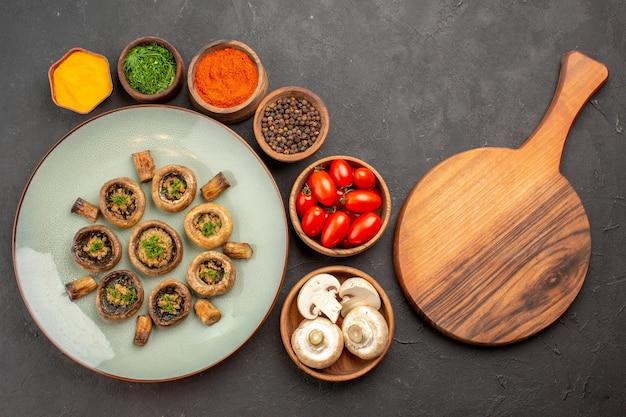 暗い床の皿に新鮮なトマトと調味料を使ったおいしいキノコの食事の上面図夕食の食事料理のキノコ