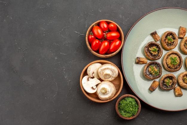 Vista dall'alto gustoso pasto di funghi con pomodori freschi e verdure su un piatto di superficie scura cena che cucina funghi