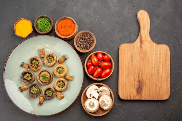 Top view tasty mushrooms meal with fresh tomatoes and seasonings on a dark surface dish dinner meal cooking mushroom