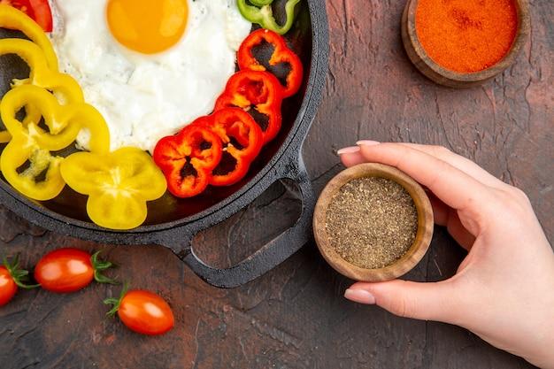 Вид сверху вкусный омлет с нарезанным болгарским перцем и приправами на темном столе