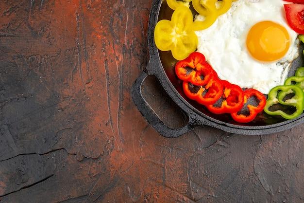 暗いテーブルの学校のスクランブルエッグの朝の朝食の色のお茶のパンのない場所にスライスしたピーマンとトマトのトップビューおいしいオムレツ