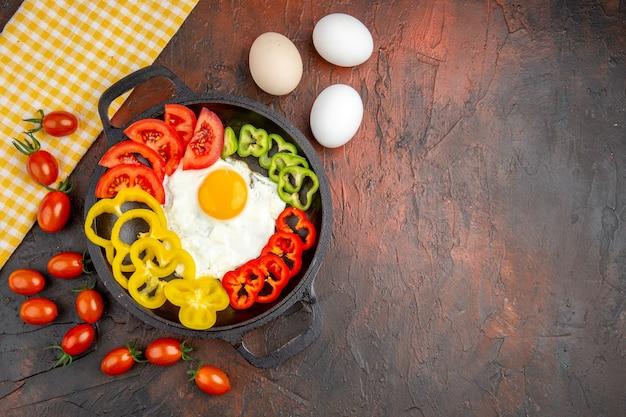 Vista dall'alto gustosa frittata con peperoni a fette e pomodori sul tavolo scuro
