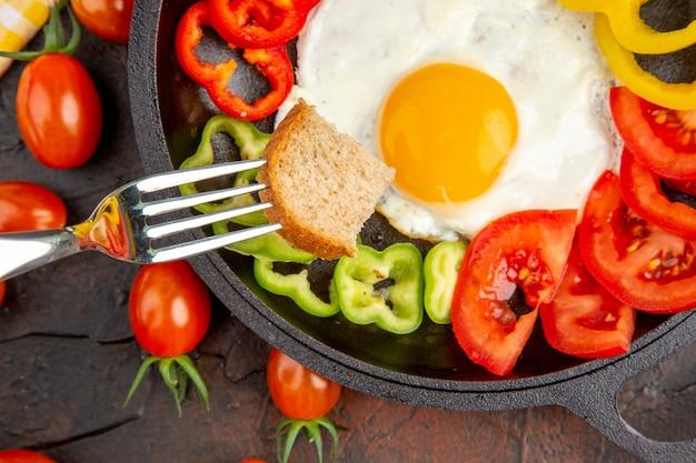 暗いテーブルにトマトとスライスしたピーマンを添えたトップビューのおいしいオムレツ