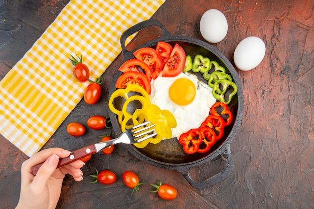 Vista dall'alto gustosa frittata con pomodori e peperoni a fette sul tavolo scuro