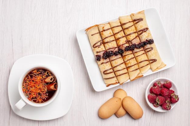 Vista dall'alto di gustosi rotoli di pancake con una tazza di tè su bianco