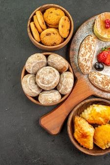 Вид сверху вкусные блины с разными сладостями на темной поверхности десерт из сахарного торта