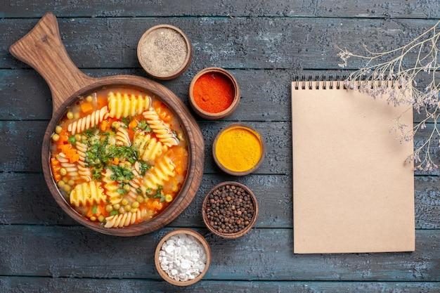 Vista dall'alto gustosa zuppa di pasta di pasta italiana a spirale con condimenti diversi sul piatto di cucina di pasta italiana di colore scuro da scrivania